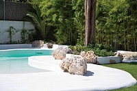 SWIMMING POOL AND ROCKS IN FRONT OF BAMBOO HEDGE