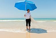A Businessman On The Beach Holding A Beach Umbrella And Surfboard, Tarifa Cadiz Andalusia Spain