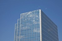 clouds reflected in the windows of a skyscraper against a blue sky, edmonton, alberta, canada