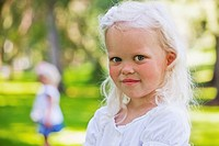 portrait of a young girl in the park with her sister in the background, edmonton alberta canada