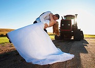 bride and groom kissing in front of a tractor, pennock minnesota united states of america