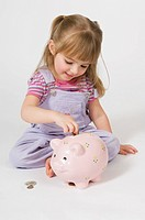 Young girl putting coins in a piggy bank