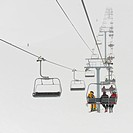 skiers riding a chairlift at a ski resort, whistler british columbia canada