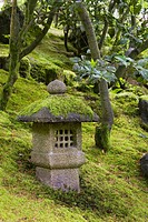 moss covered stone lantern on a hillside with trees in the background, portland oregon united states of america