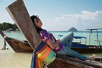 a girl relaxes on a boat on the shore, phi phi islands thailand
