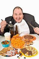 Overweight man sitting at a table full of junk food