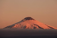 Chile, Villarrica Volcano with snow covered peak at sunset above the clouds