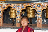 Infantile Buddhist monk standing by the prayer mills in the Temple of Fertility Chimi Lhakhang, Lobesa, Bhutan