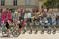 France, Vaucluse, Avignon, Cour Saint Jacques, bicycles free access to an iron gate, girls posting their bike stand, Velo Pop
