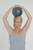 Young woman holding an exercise ball with both hands on her head