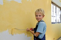 Boy, 8 years, painting a wall