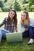 Young smiling girls sitting on the grass with a laptop