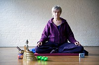 Older woman, meditating in an empty room, using Buddhist techniques.