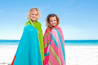 Smiling children on the beach wrapped in their towels