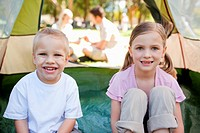 A happy pair of kids sit inside the tent as their parents are just outside