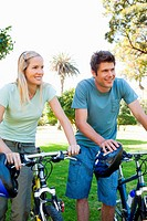 A couple standing beside their bikes smiling