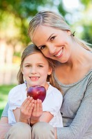 Close up of a mother holding her daughter who is holding an apple