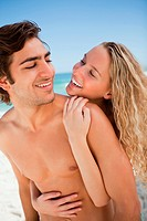Young couple smiling while embracing each other on the beach