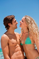 Young couple standing on the beach while smiling at each other