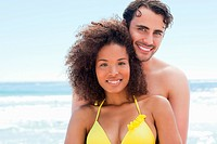 Man in swimsuit smiling as he embraces his friend