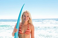 Woman smiling while holding a surfboard