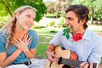 Man with a rose in his mouth playing the guitar for his girlfriend