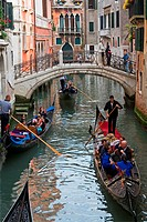 Tourists taking gondola rides on one of the many canals of Venice, Italy.