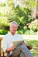 Man looking to his side while holding a tablet as he sits on a bench