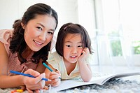 Mother and daughter look forward as they take a break from colouring