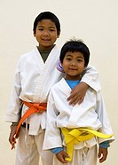 Two young sibling boys in white martial arts gi´s, elder with orange belt, younger with yellow belt. Older child has arm around shoulders of younger c...