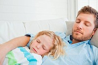 Close up of a man and his son asleep on the couch