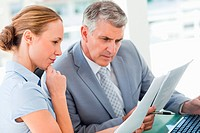 Man and a woman intently studying business reports