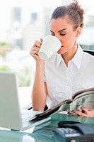 Businesswoman drinking a coffee while holding a newspaper