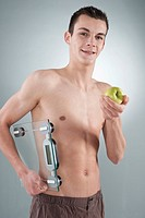 Young man with a bare torso, holding an apple and a set of scales