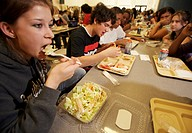 Middle school junior high, students eat in the cafeteria. One student foreground eats a salad as the pizza_eaters look on. Winston_Salem, NC.