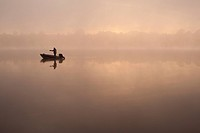 Sunrise Lake Cassidy in fog with fisherman in small boat fishing Snohomish County, Washington.