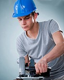 Young tradesman using a jigsaw