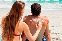 Rear view of a woman applying sunscreen on her boyfriend