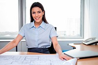 Portrait of pretty female architecture sitting with blueprints on desk