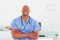Smiling doctor in scrubs with arms folded in his examination room