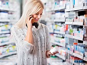Woman holding medication container while talking on cell phone