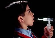 Young boy using inhaler for respiratory problem.