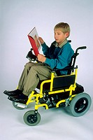 A 7_year_old handicapped boy reading a book in a wheelchair.