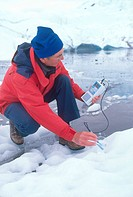 A scientist measures the pH of glacial water.