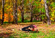 Woman exercises in the autumn forest yoga ashtavakrasana pose