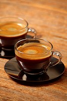 Photo of two cups of espresso on an old wooden table. Selective focus on first cup.