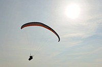 Paraglider in front of the sun