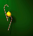 a gold 3D bauble with two christmas candy canes against a green background ready for christmas