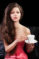 sophisticated young pretty brunette in pink elegant dress sitting on a black sofa and tasting a cup of tea. she looks in to the lens and takes of tea ...