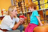 woman with child choosing and trying on new boots in shopping supermarket